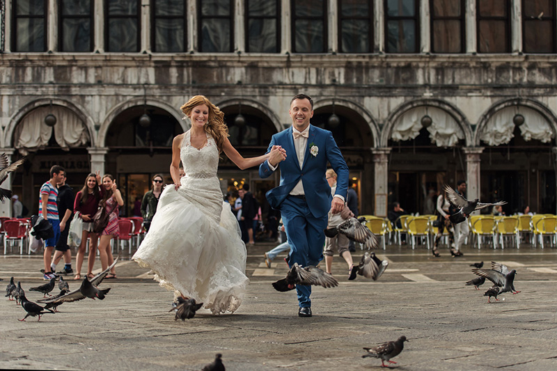 bride and groom runnig on san marco