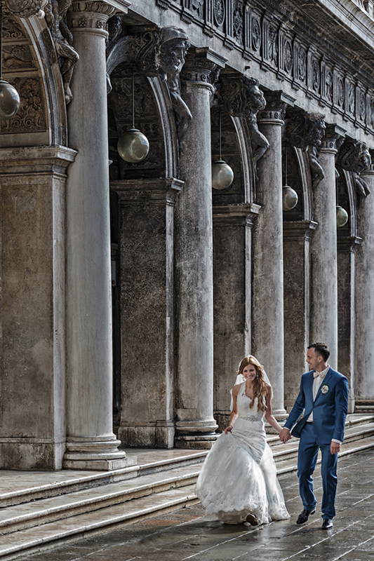 bride and groom walking in front doges palace near caffe florian at san marco square