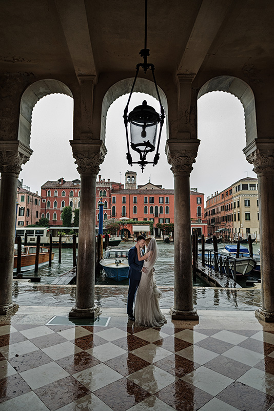 bride and groom taking cover in front of library in grand canal