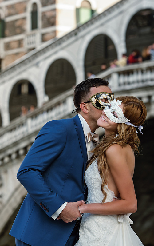 groom kissing bride at terrace in front of rialto bridge covered with original venice mask