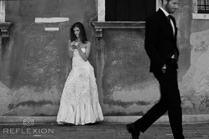 fashion shoot bride at wall in venice groom is passing by