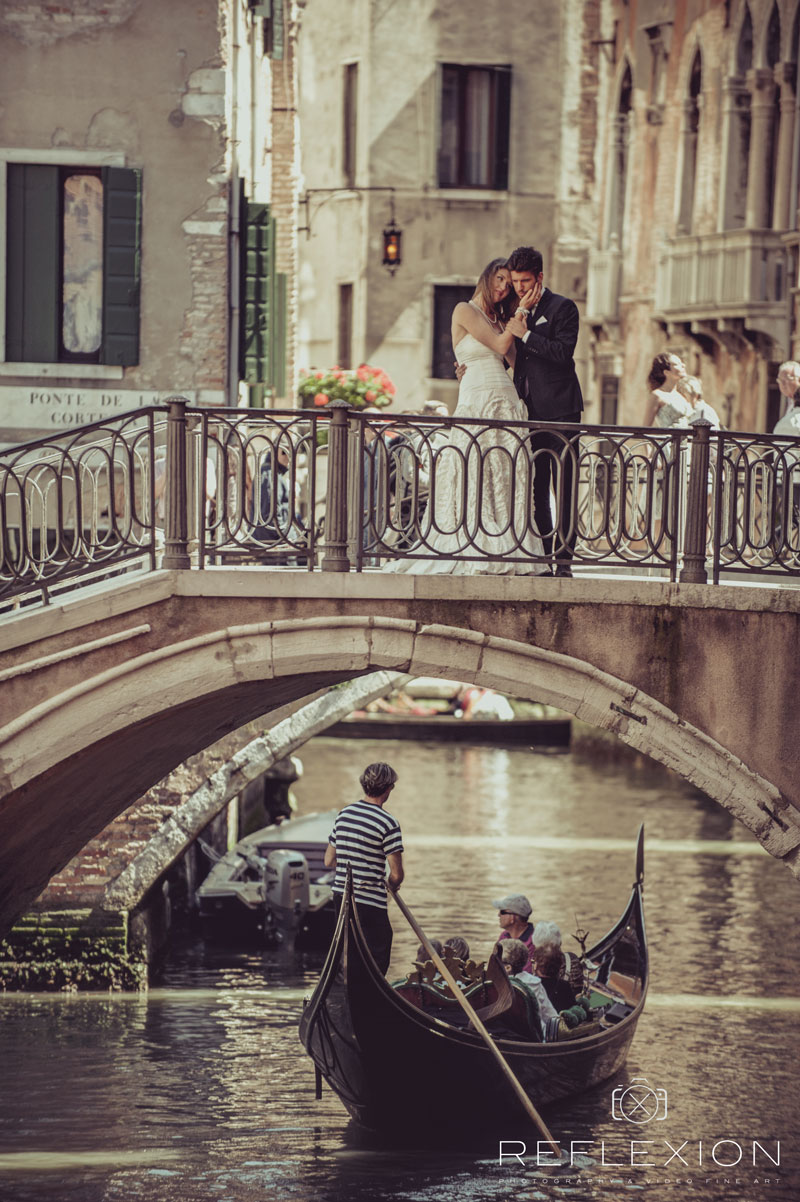 honeymoono in italy brode and groom together staying on the bride gondola passing