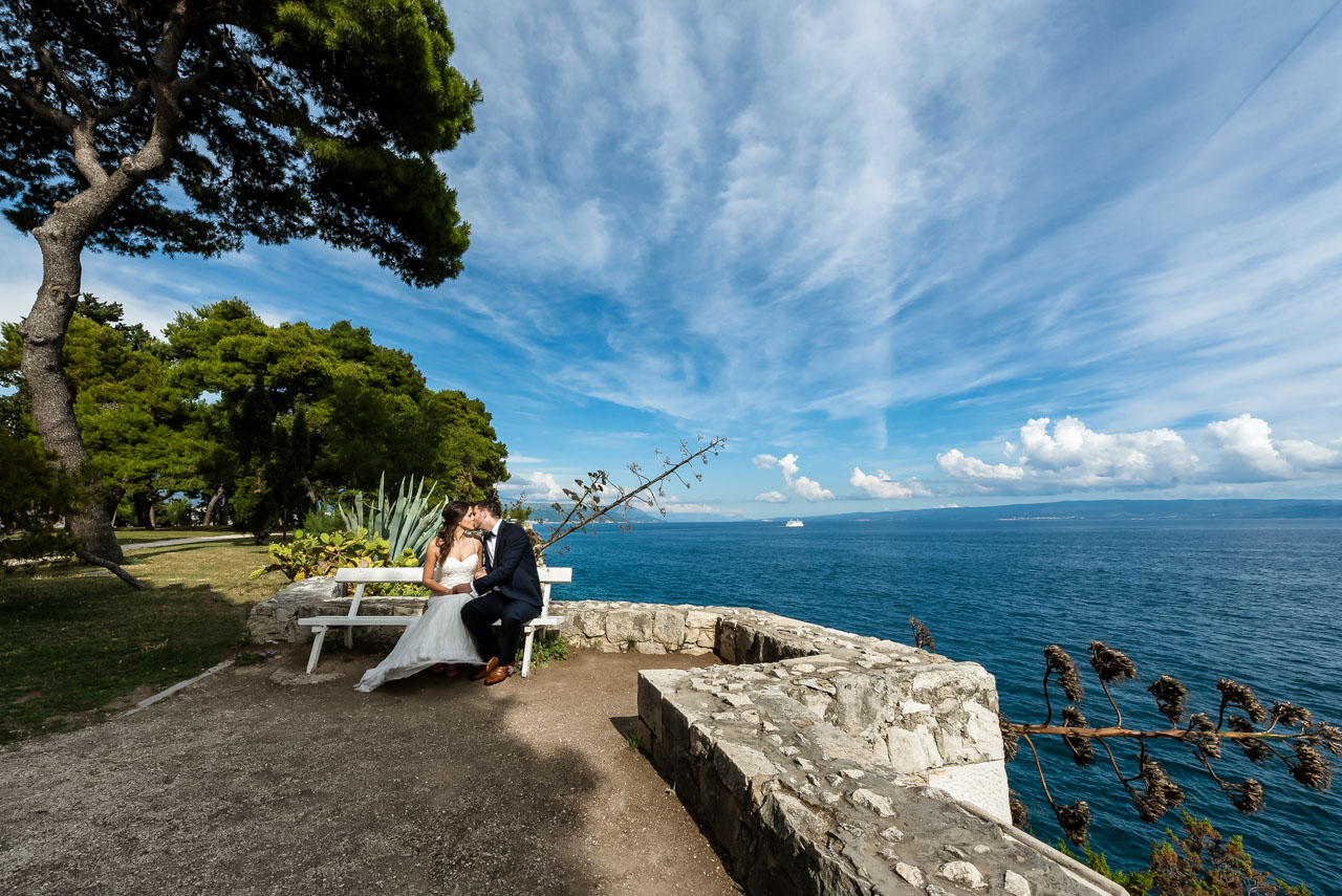 Wedding Photographer Split Croatia bride and groom kissing on the bench