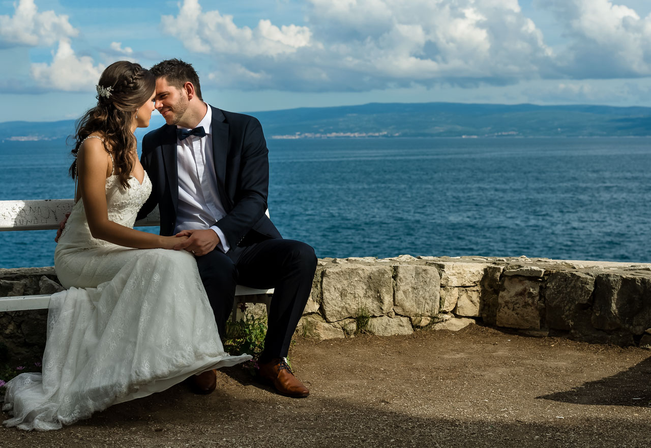 Wedding Photographer Split Croatia bride and groom siting on the bench hvar island in background