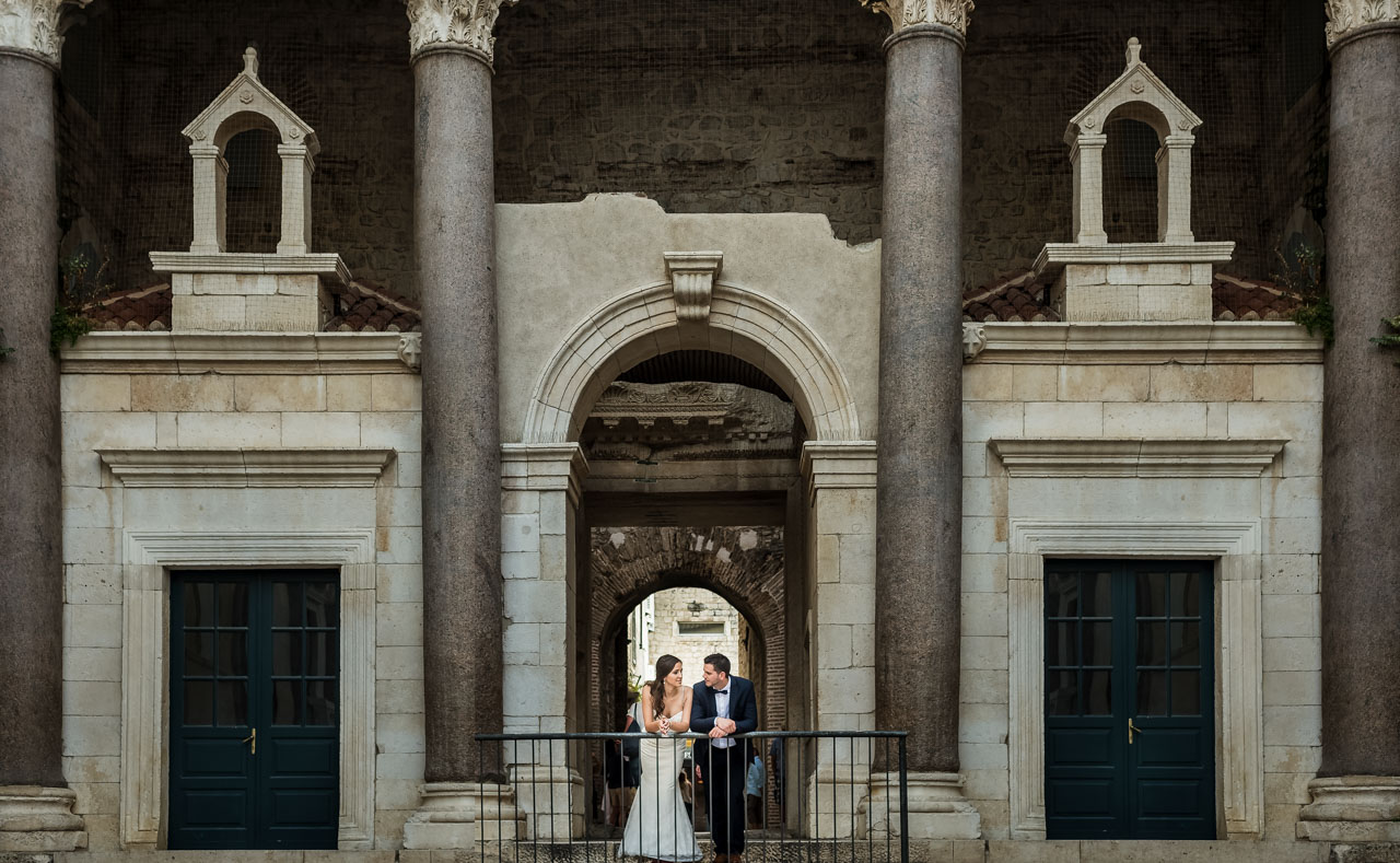 Wedding Photographer Split Croatia bride and groom holding each other old city enterance