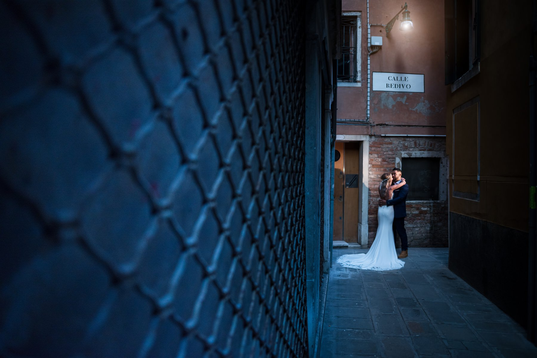 Palazzo Cavalli Venice bride and groom kissing with blue textured wall