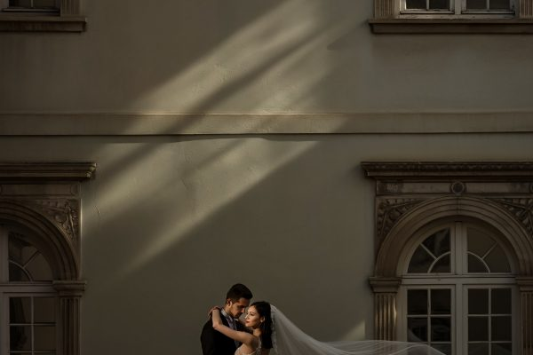 bride and groom in kissing pose in front of building in Dubrovnik