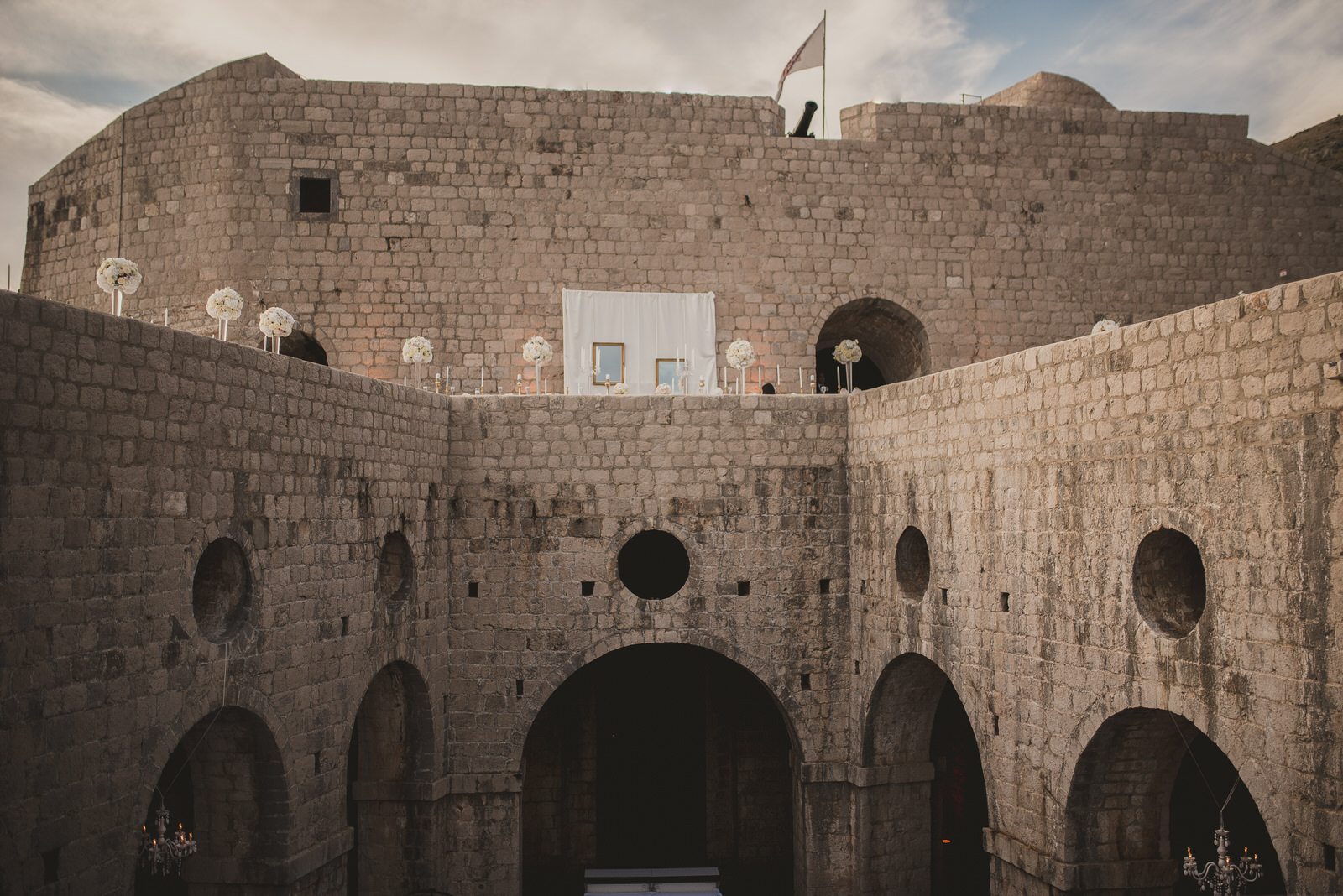 inside Fort Fovrijenac in Dubrovnik with white flowers decor on the wall before wedding ceremony