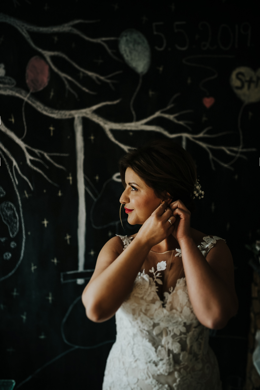 bride Simona standing in front black wall with tree decore