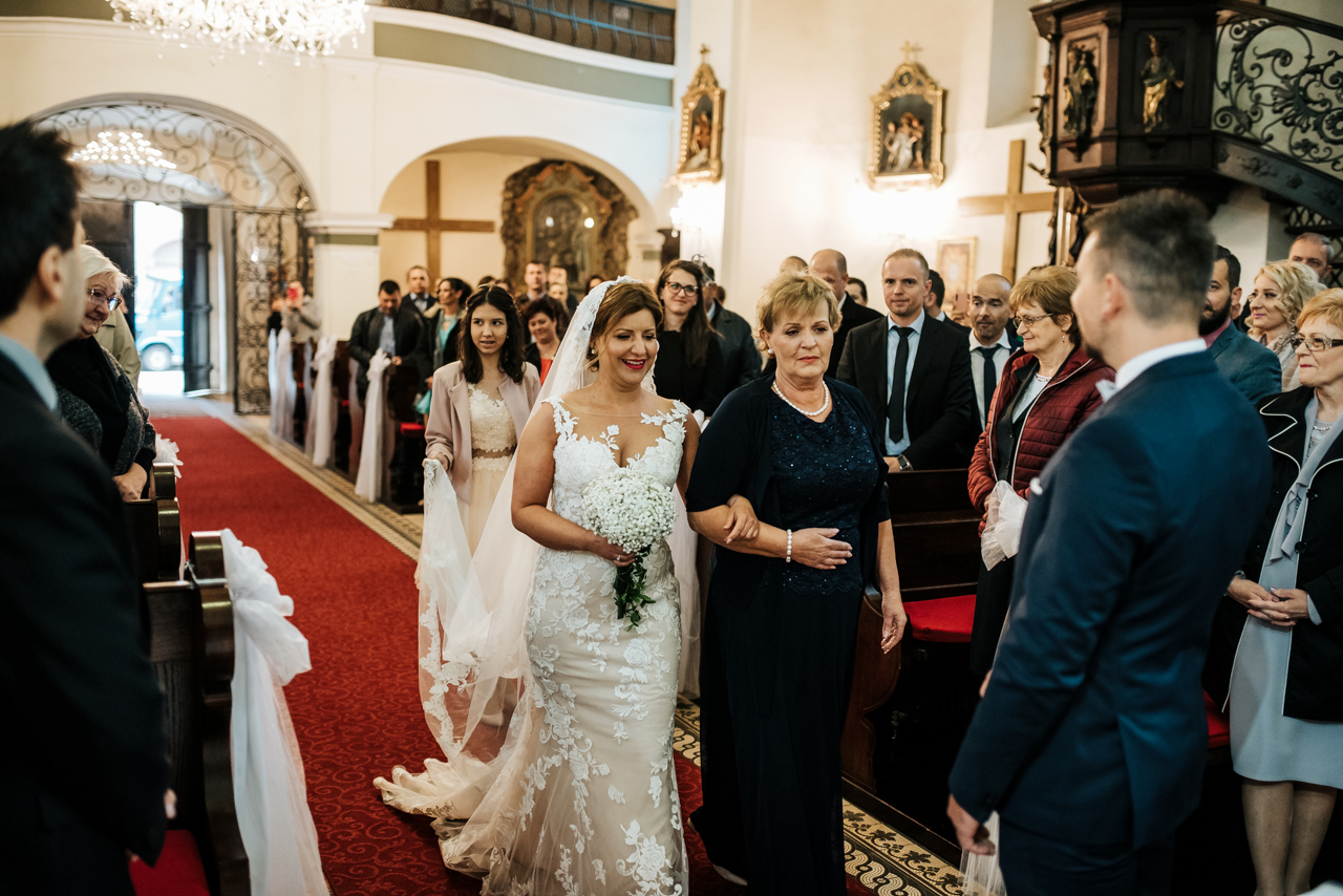 bride walking down the aisle with her mum in st nicholas church varazdin