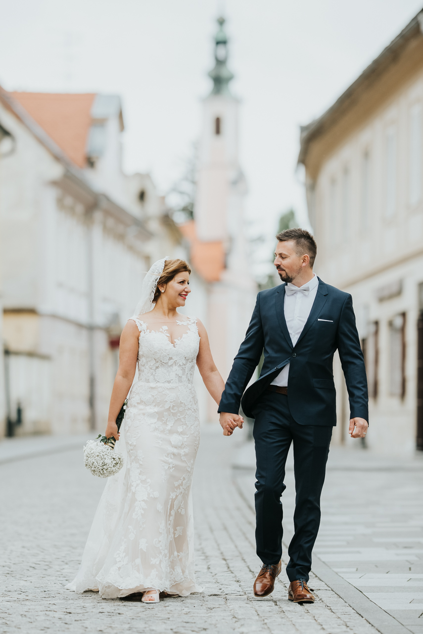 bride and groom walking in the streets of varazdin looking each other