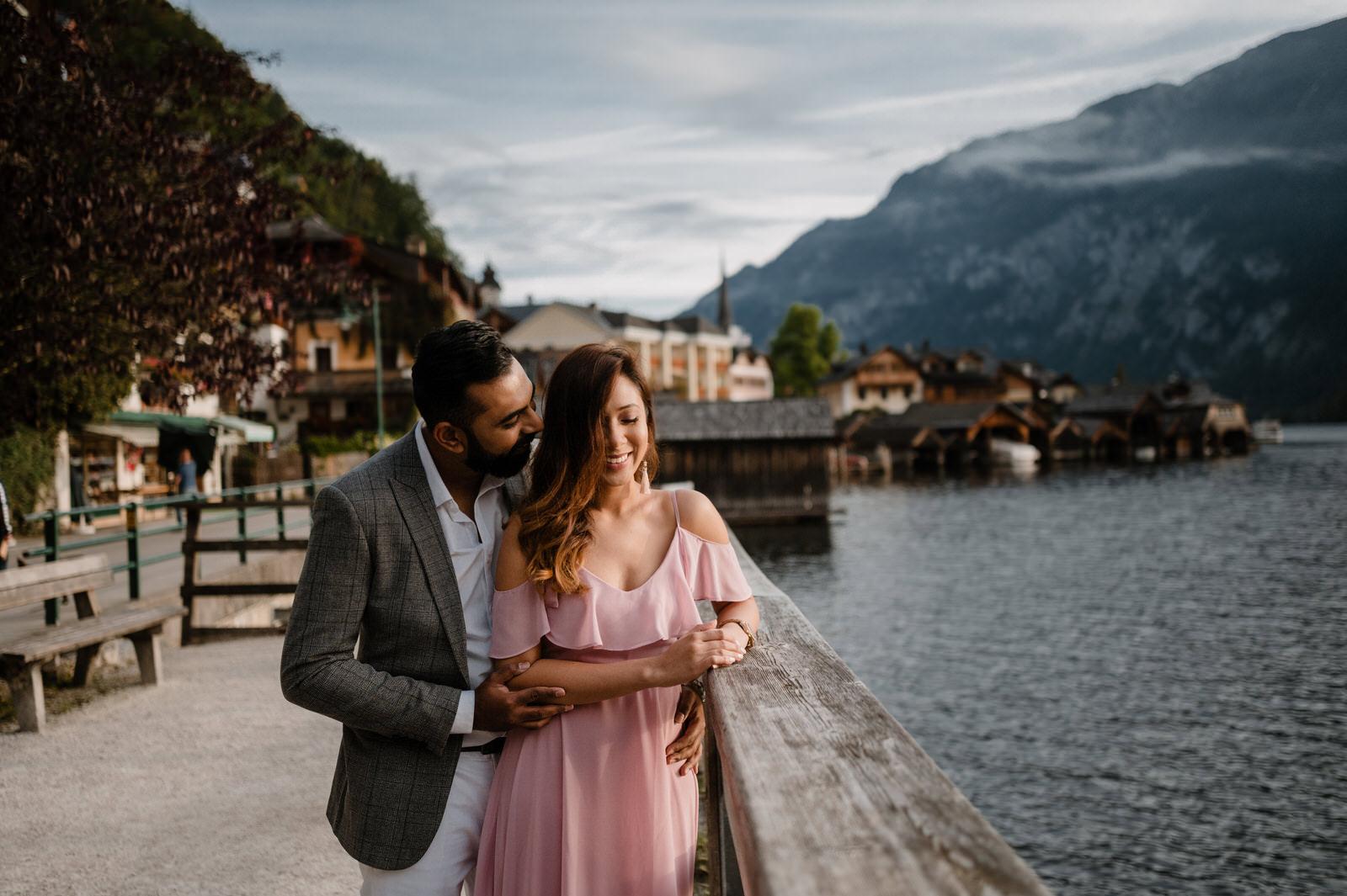 Couple Visha and Kishan standinh at the dock in Hallstatt with beautiful panorama