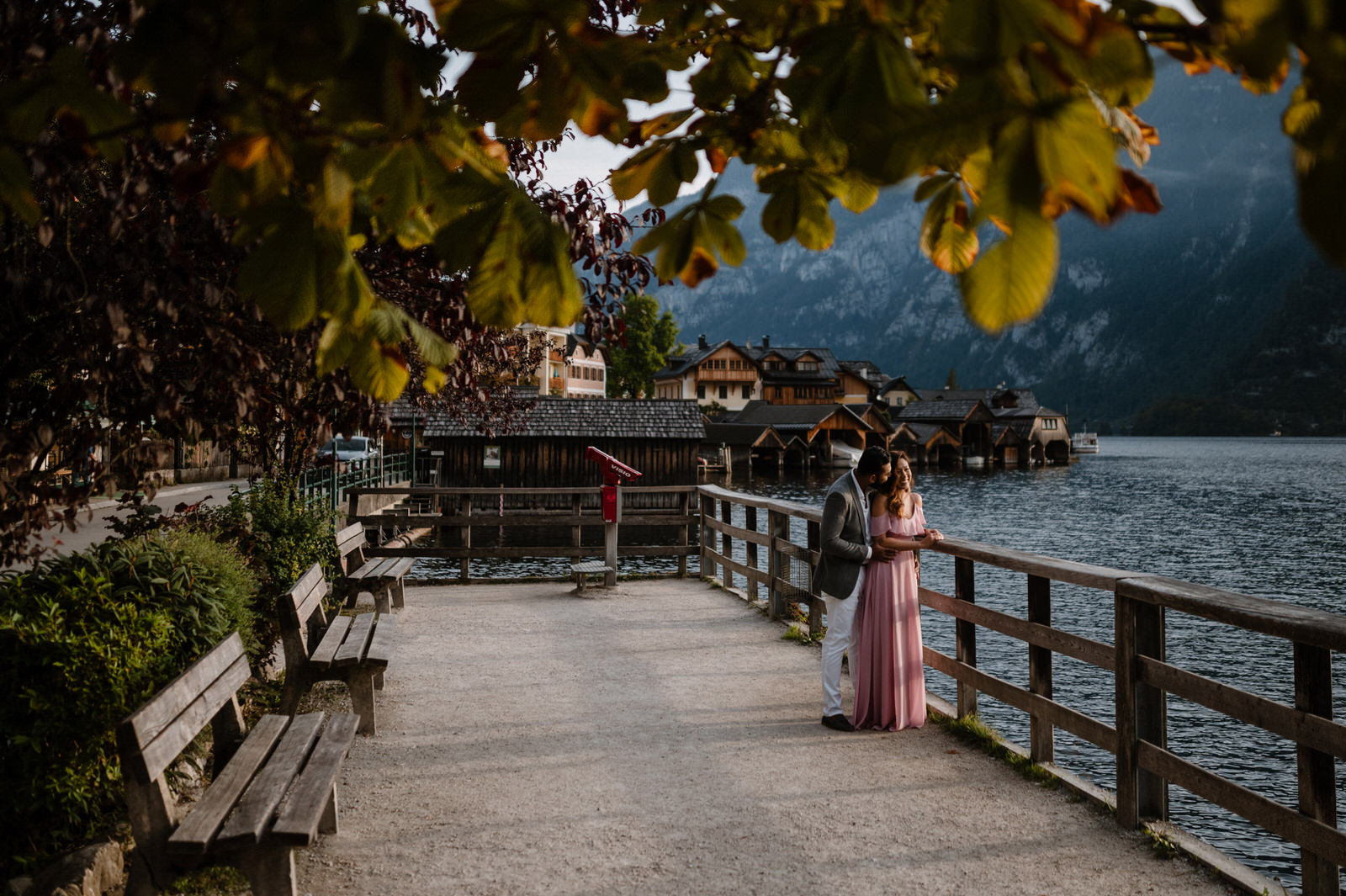 cuople standing at the dock edge and looking the lake of Hallstatt
