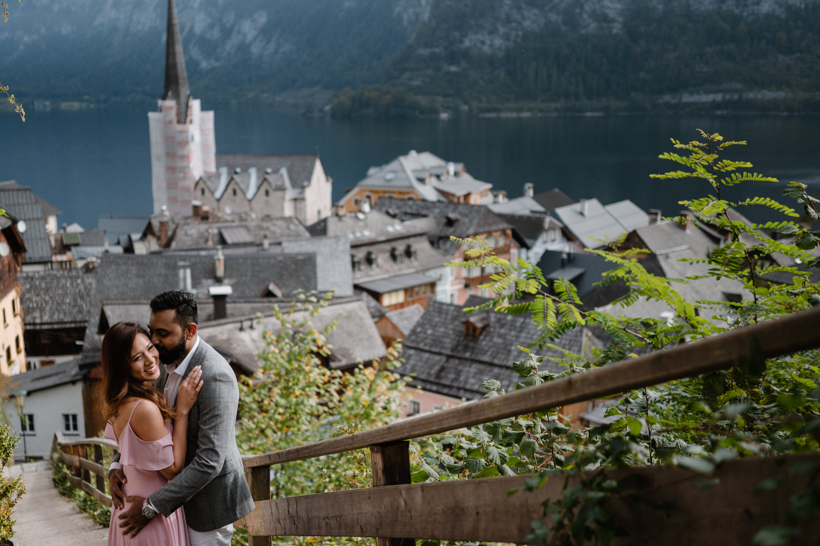 couple together smiling standing on the stairs and watching hallstatt