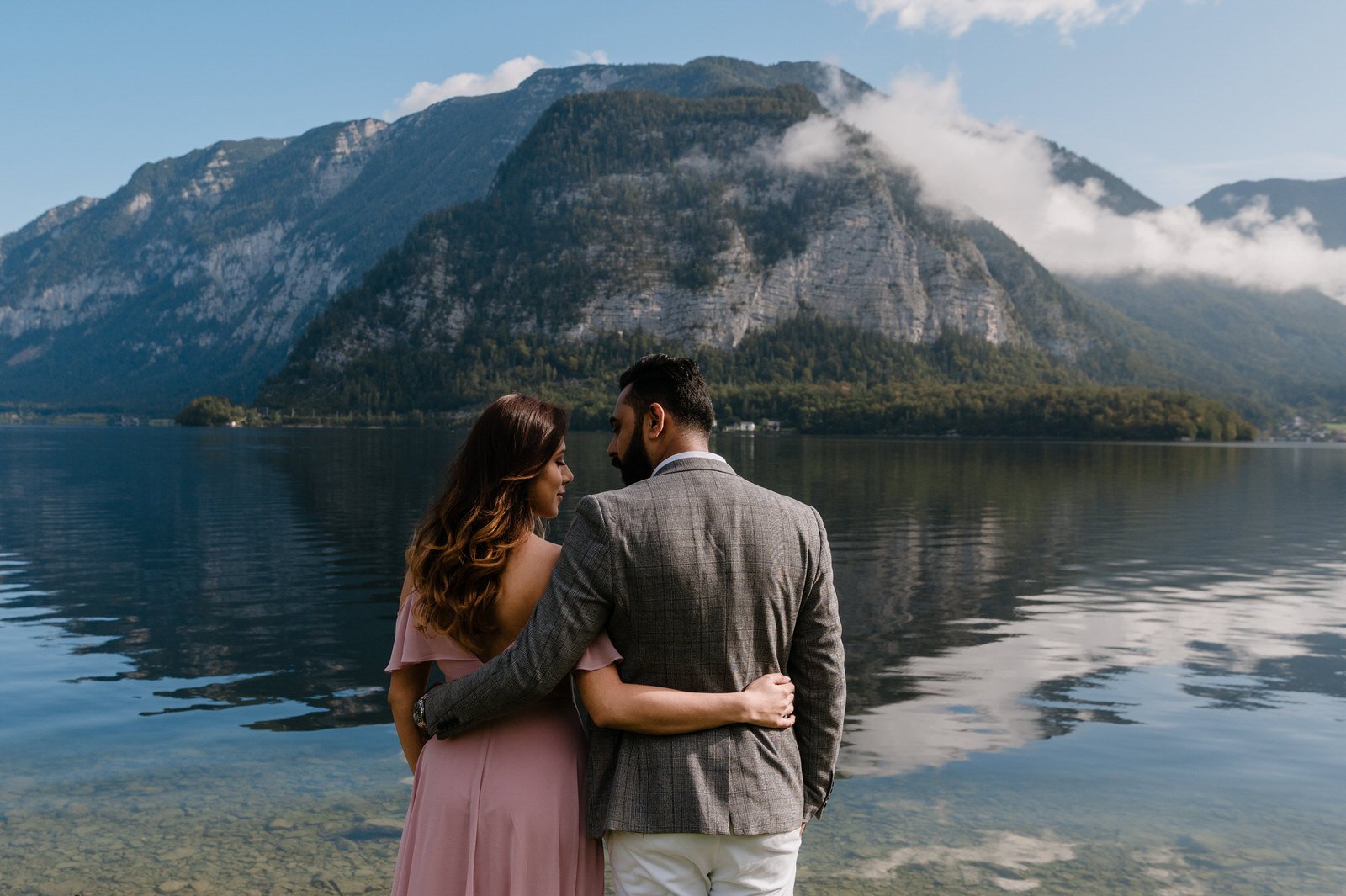 couple shoot from the back looking each other with mountain in background