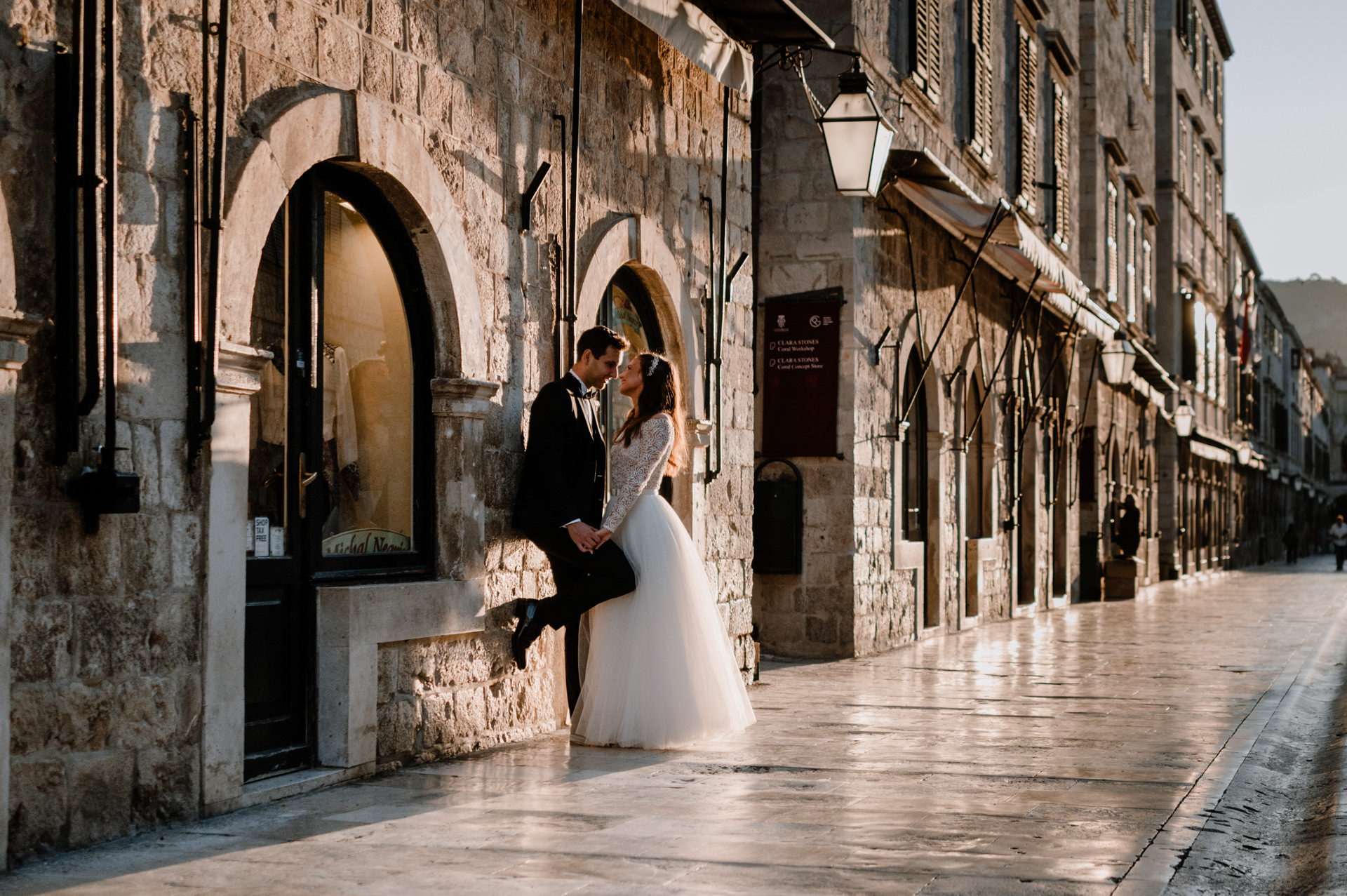 bride and groom looking at each other in front of the store at stradun street
