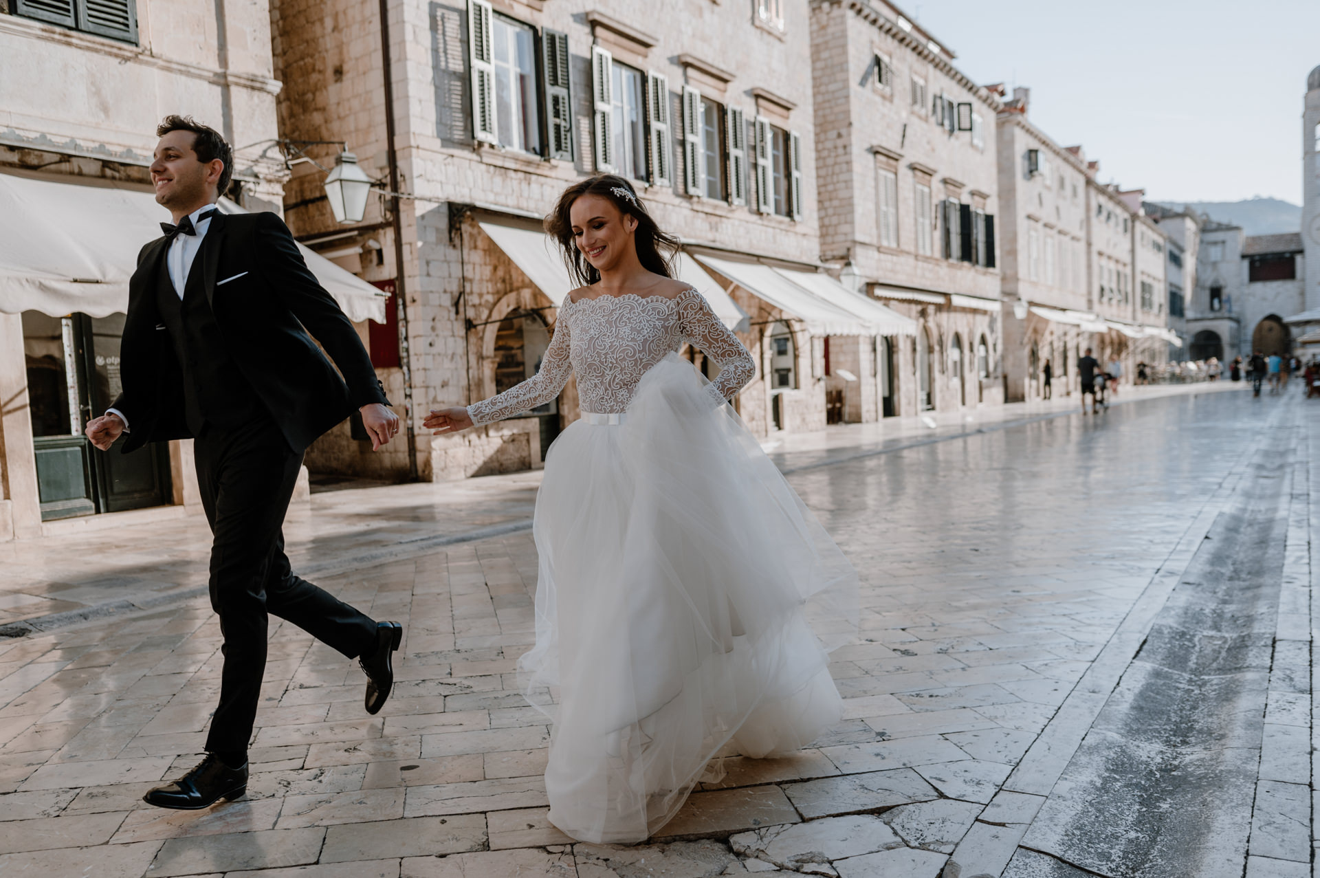 bride and groom running down the street