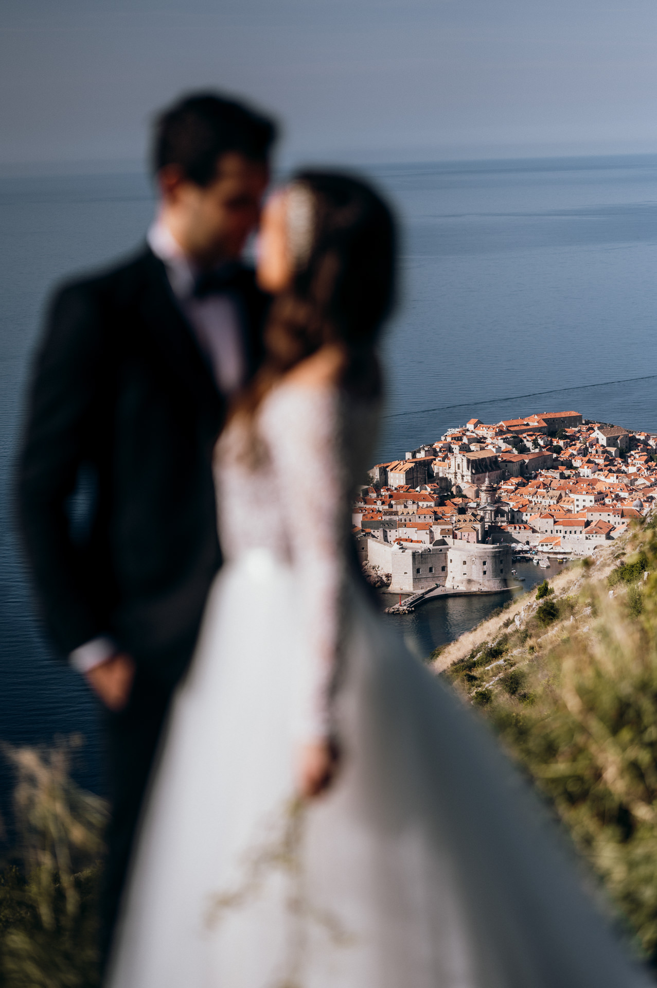 bride and groom together focus on the city of dubrovnik